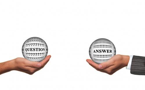 Dwie dłonie na której leżą kule z pytaniami: question i answer.