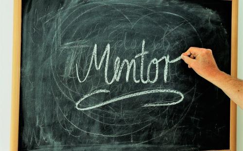Tablica szkolna i podpisany na niej kredą napis: Mentor.